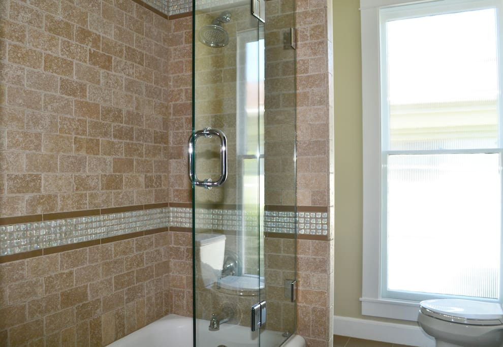 Full bathroom with bathtub and shower. Armoire contains toiletries/hairdryer.