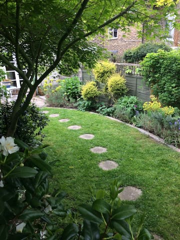 Sunny garden with lawn and colourful borders. There are two patios, one at either end, for eating, and an in-built barbecue near the house