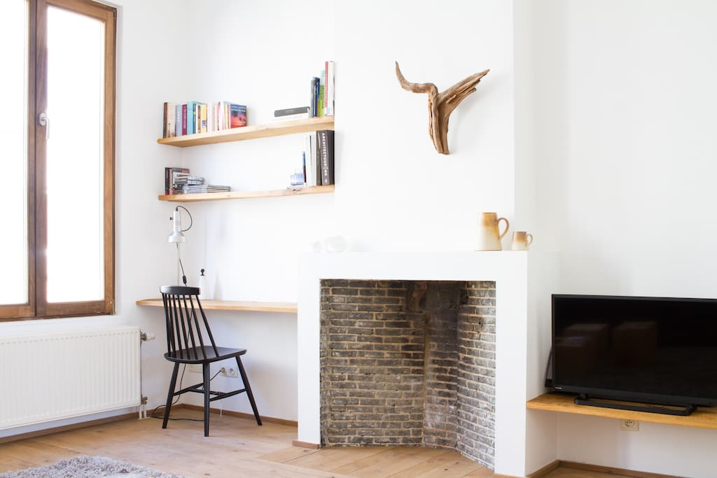 Old fireplace  / desk with library / tv + stereo