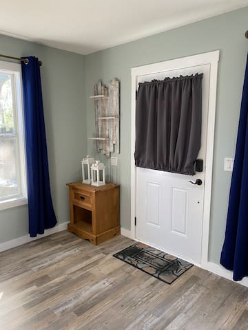 This room's PRIVATE ENTRY door leads right outside onto a cement deck. A paved walkway leads around the house to the driveway.