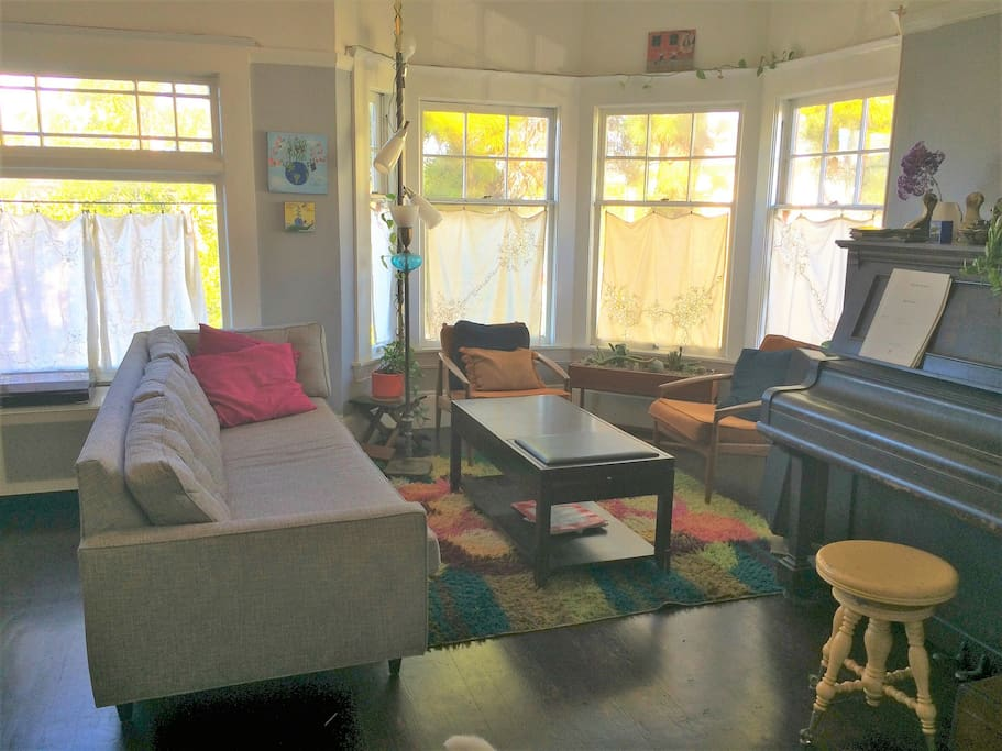Sun-filled living room with upright piano