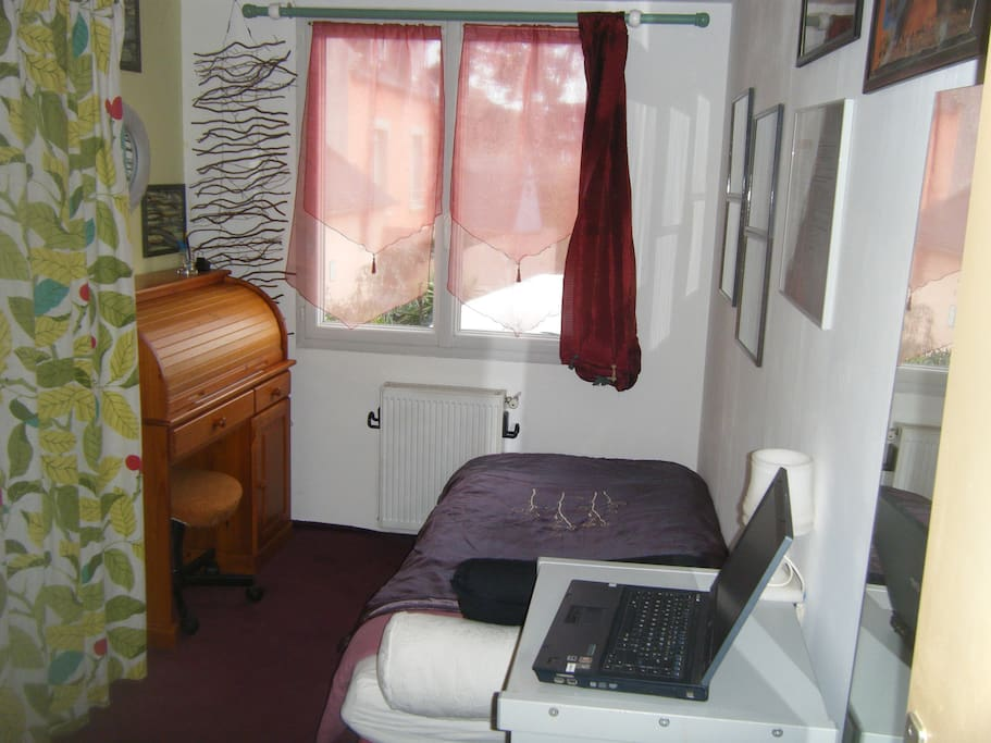 Chambre 2 - 1 lit d'une personne et un bureau bien éclairé.