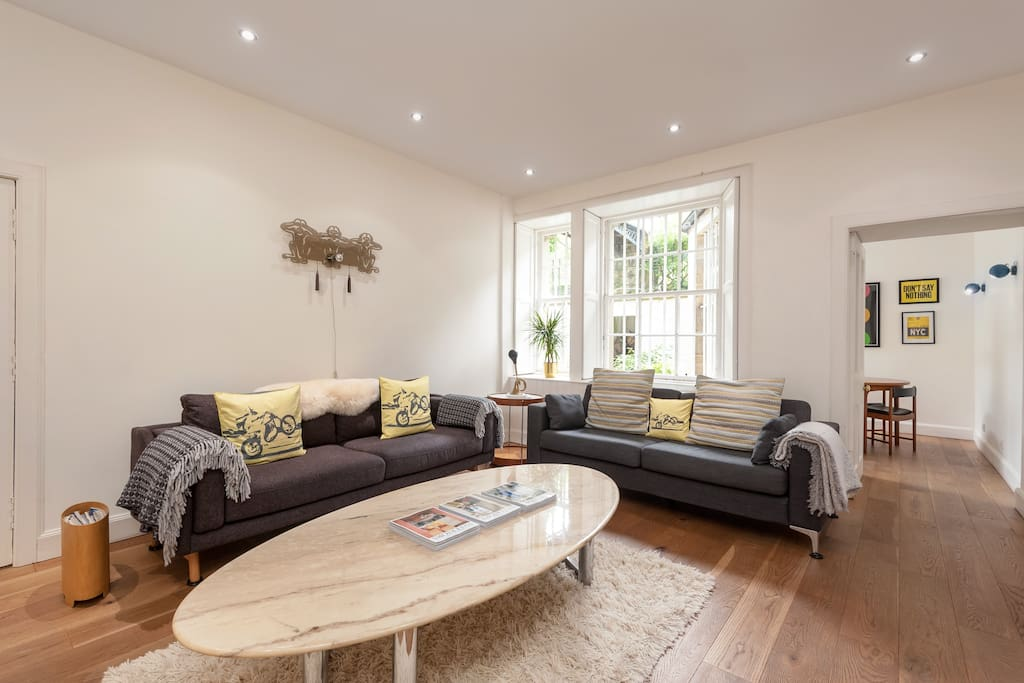 Spacious sitting room with two 3 seater couches, overlooking back courtyard