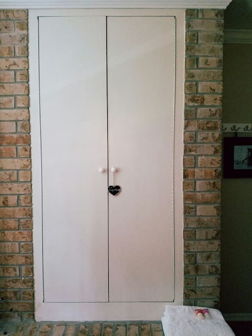 Closet space in converted fireplace.  Luggage stand and hooks for your convenience.