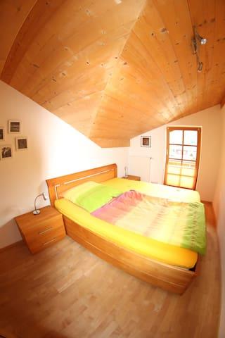 Gemütliches Schlafzimmer mit Holzbett. Zugang zum kleinen Balkon.