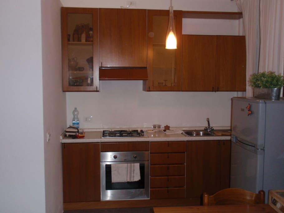 Angolo cottura fornito di cucina Scavolini, con 2 finestre ai lati del frigorifero