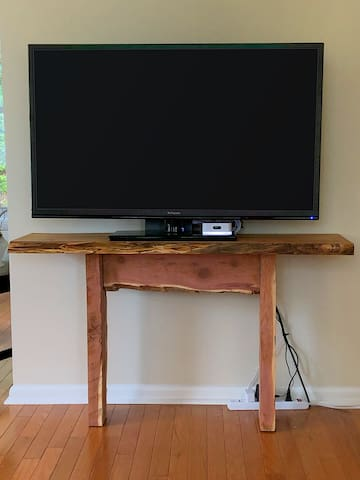 Kick back with the 50-inch TV (includes Blu-Ray and Chromecast media players) on an artisanal live-edge console table sourced from local hardwood