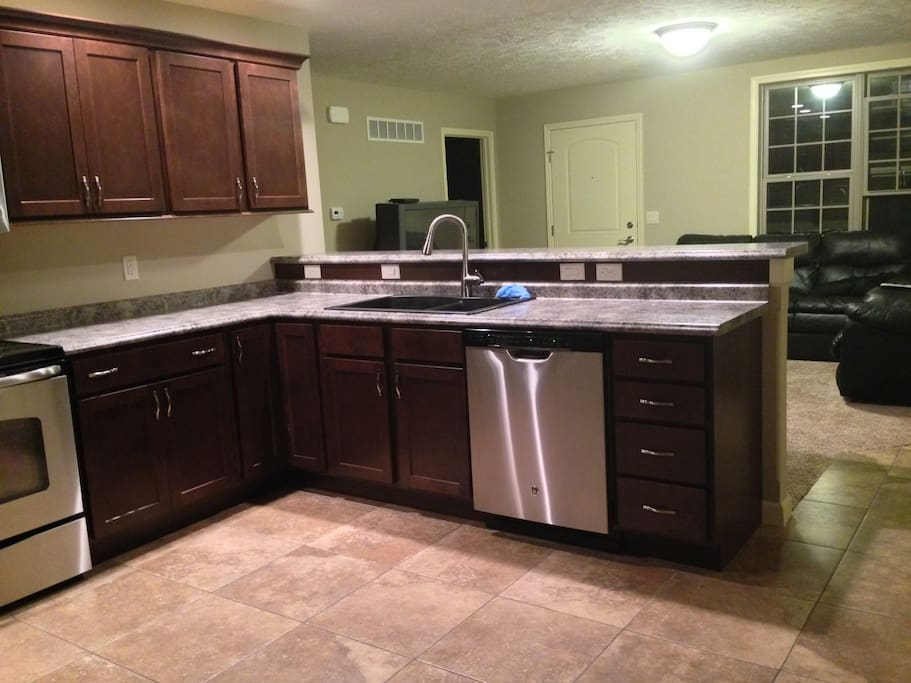 Kitchen includes a dishwasher and overlooks living room.
