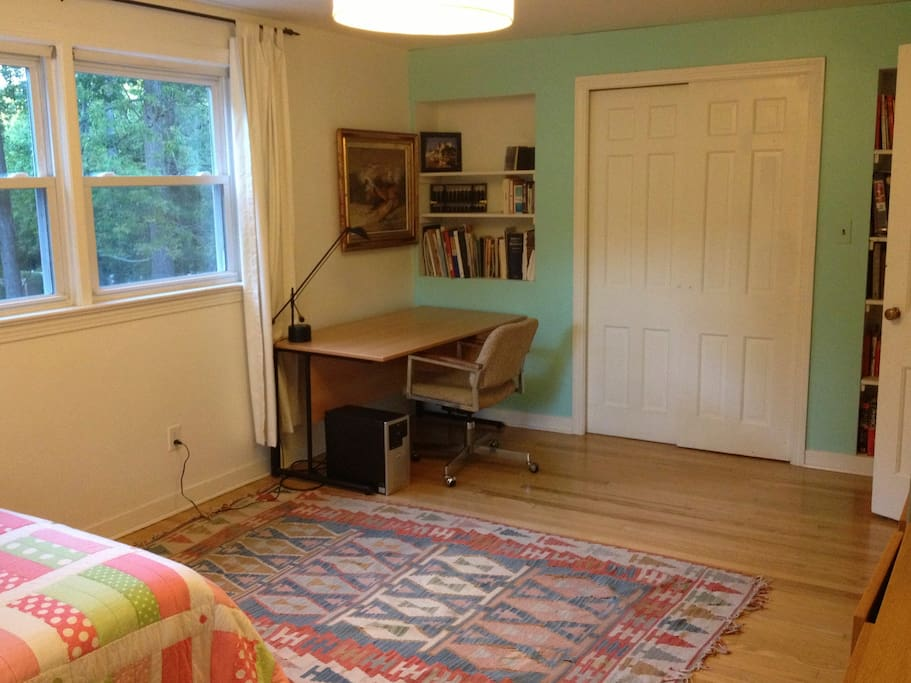 There is a desk, a large closet and an armchair.