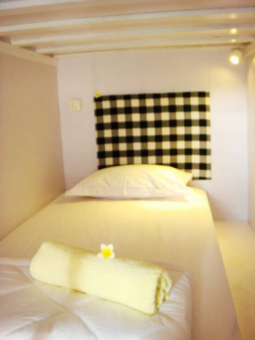 Headboard with black and white Balinese pattern. LED reading light and power outlet in each bed. A double hook for your shorts/ t-shirt is also provided