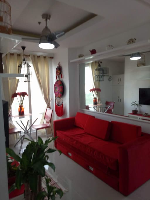 Bright and decorative living space, TV set  , comfortable lounge chair and a dining set for two.