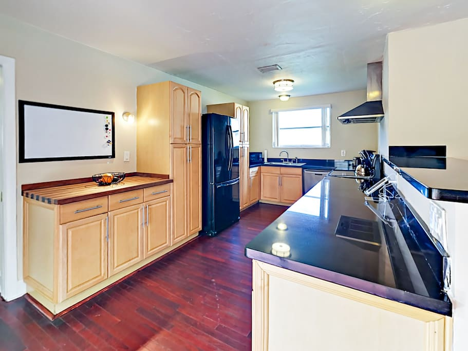 The well-equipped kitchen boasts gleaming black granite countertops and high-end appliances.
