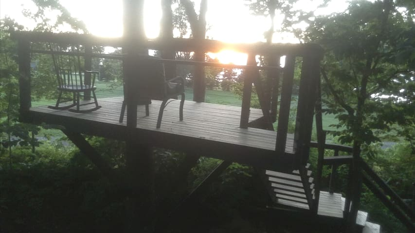 Elevated sunset deck.  With clear  views of lake Ontario and Spectacular Sunsets guests can relax on this recently built treehouse style deck.