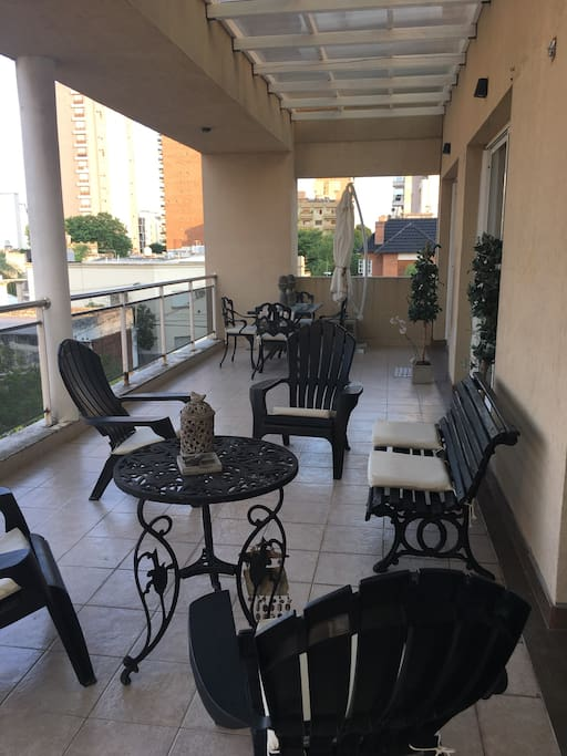 Balcón con mesa y sillas con acceso a cocina.