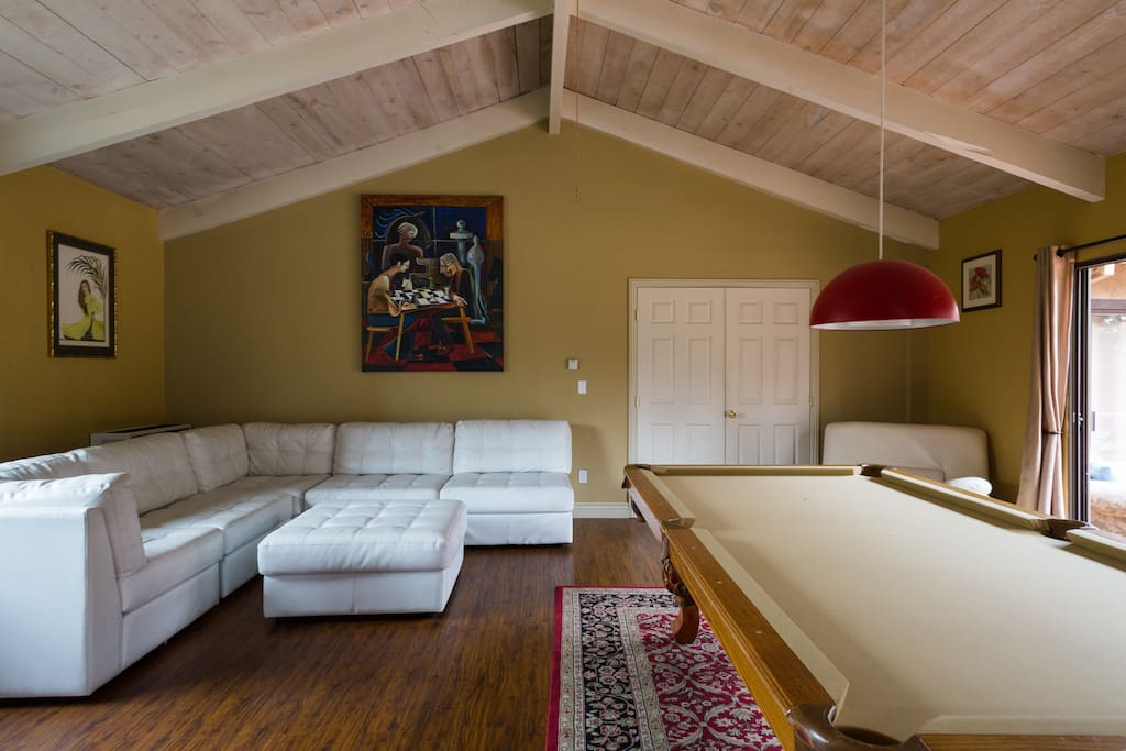 Game Room with pool table, modern leather sectional and ottoman