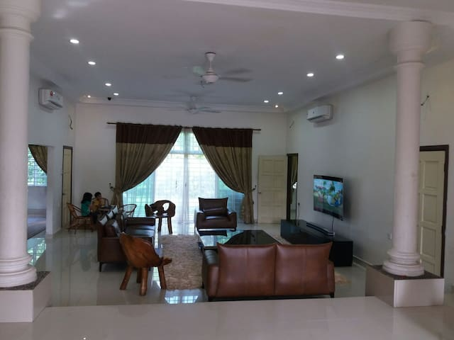 Comfortable living area with 6 seater leather sofa and WiFi 65 inches curved samsung TV.