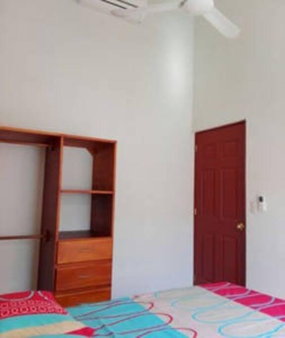 Recamara número 1 cuenta con una cama matrimonial, closet, aire acondicionado y ventilador de techo.