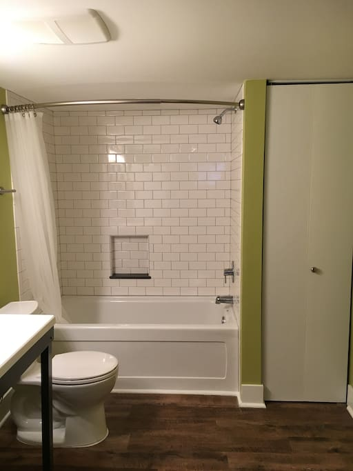 Newly finished tub/shower with custom made vanity with wheel under access and new washer/dryer