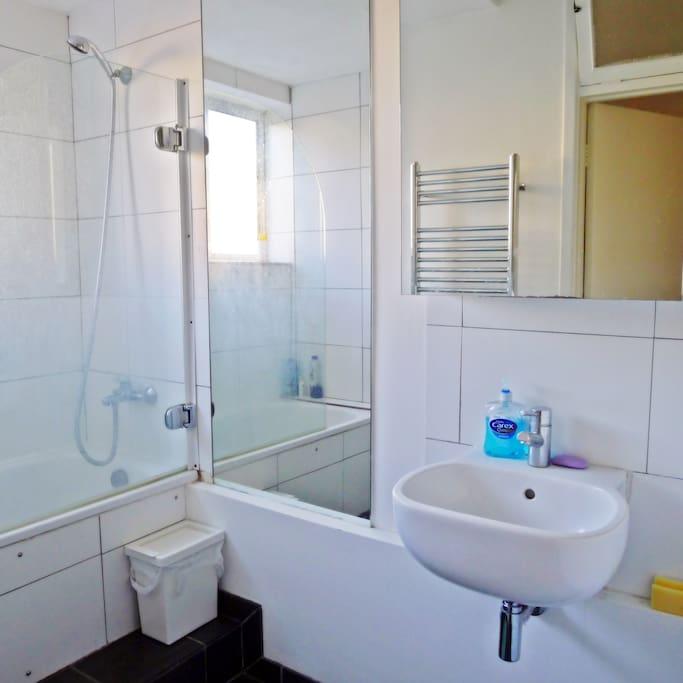 A shared bathroom with a bath tub, a basin, and all toiletries