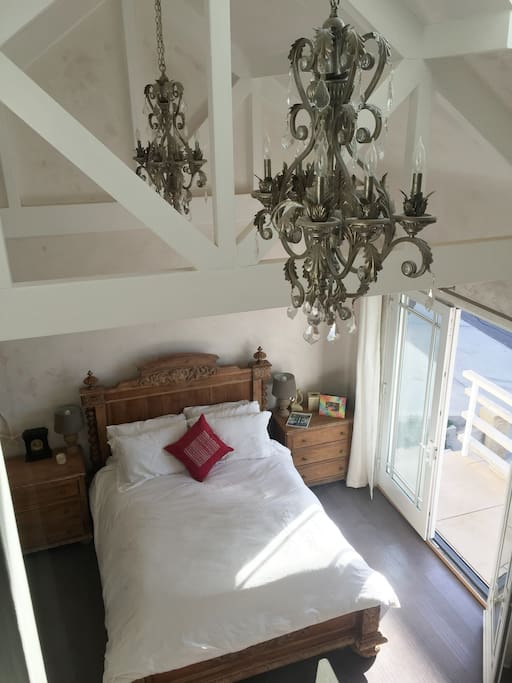 Bedroom with vaulted ceilings, artisan plaster and french doors to patio