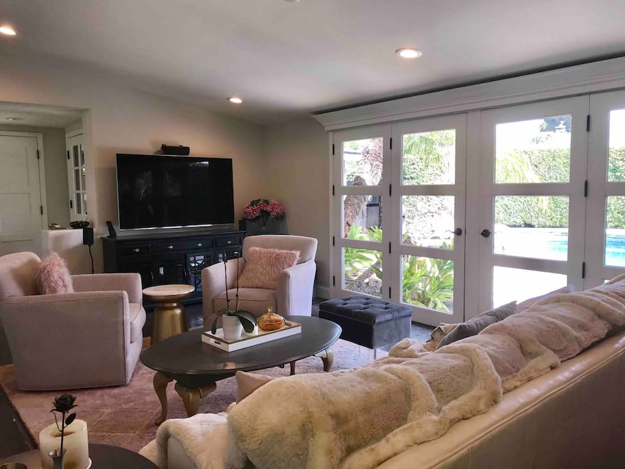 """Shared living room with 65"""" Ultra HD TV with Sonos Sound System that walks out to the pool for inside/outside living at it's finest."""