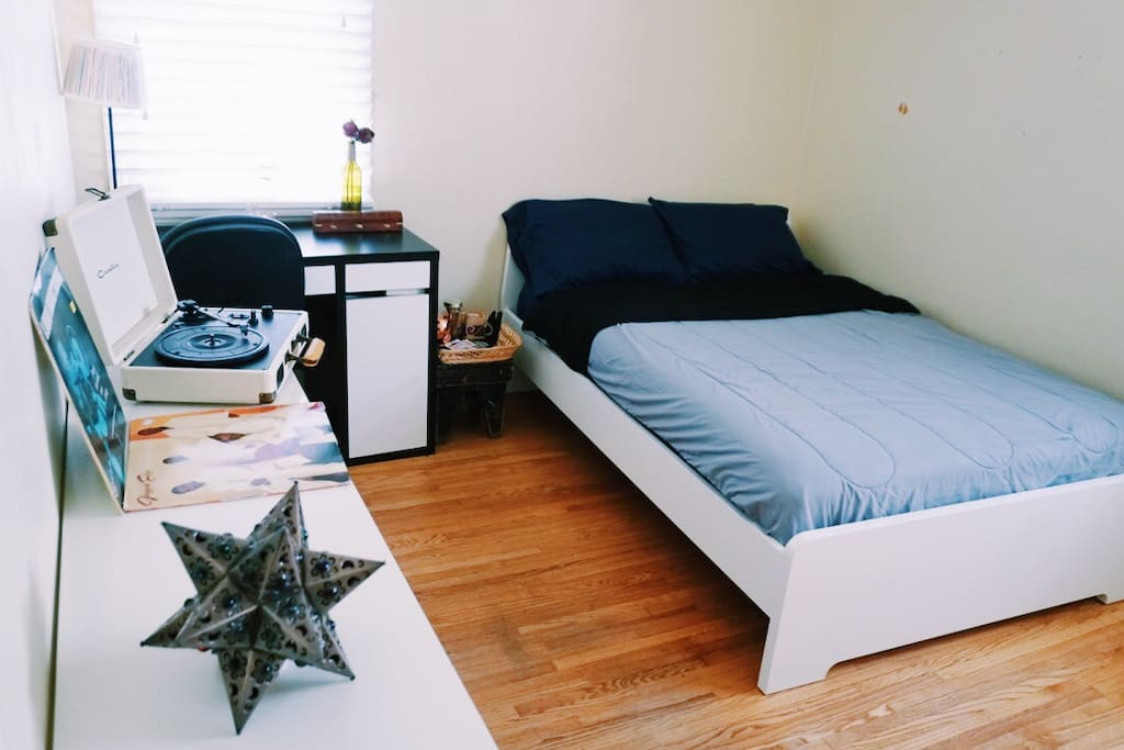 Queen sized bed with desk, and bed-side stool with tea, water, and snacks.