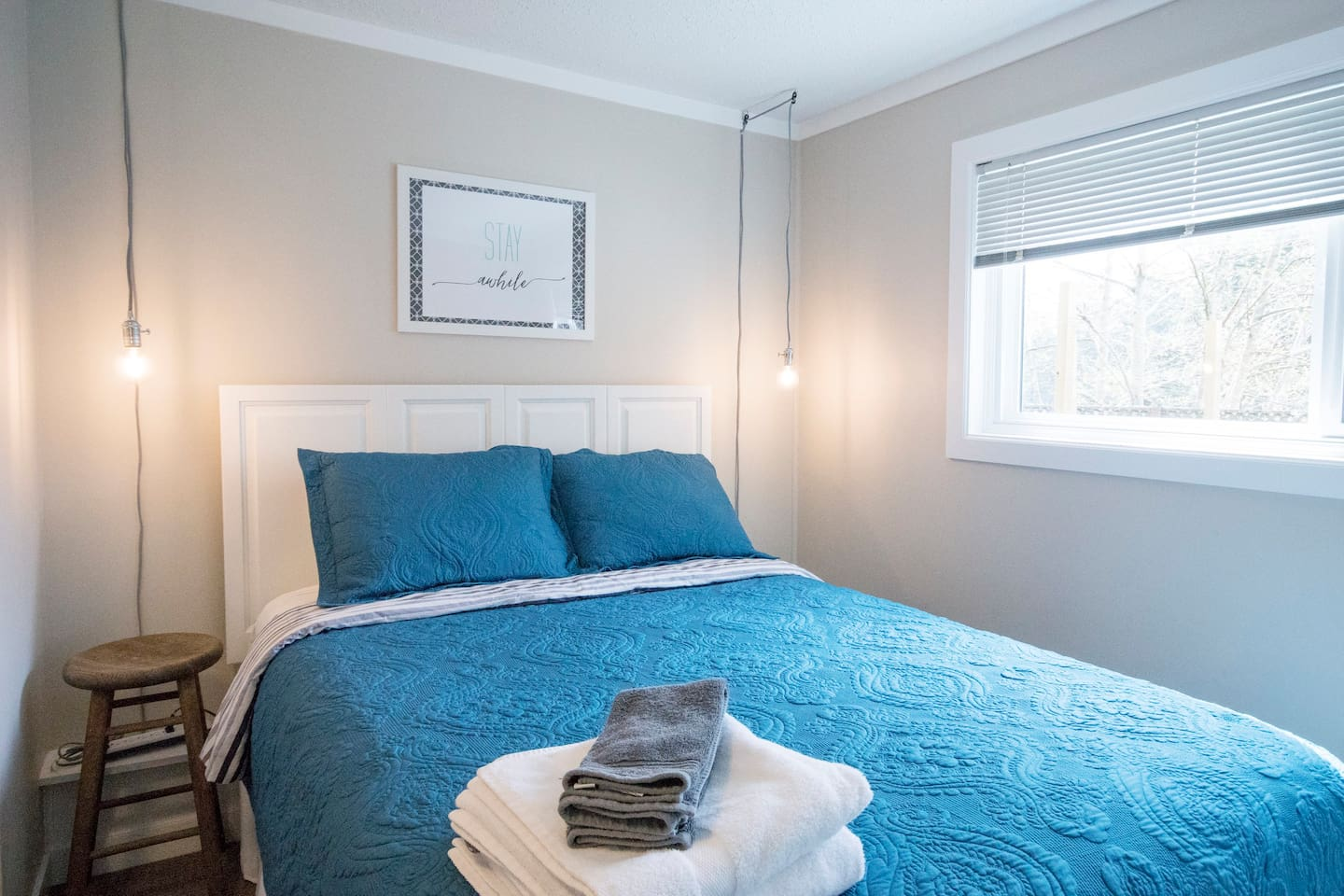 Queen sized bed with 4 pillows, duvet, and coverlet on top.  Room has closet and dresser.  Ensuite bathroom is off of bedroom.