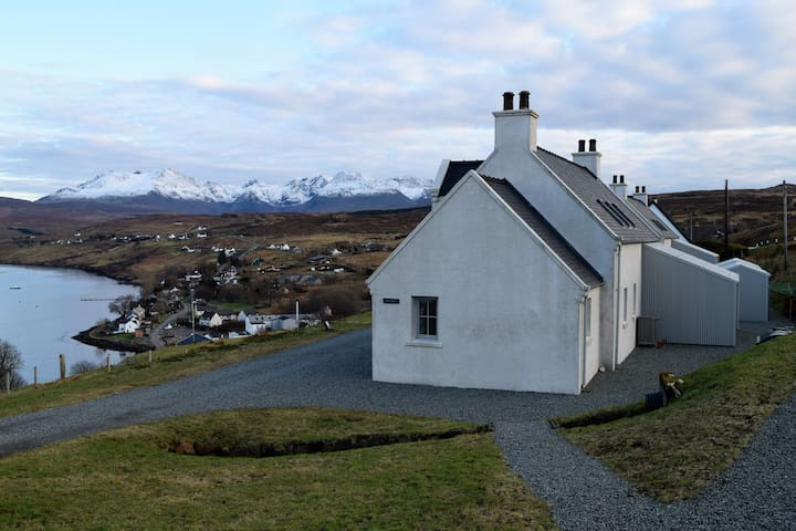 Side view of Heatherbell with the village of Carbost and distillery in the distance