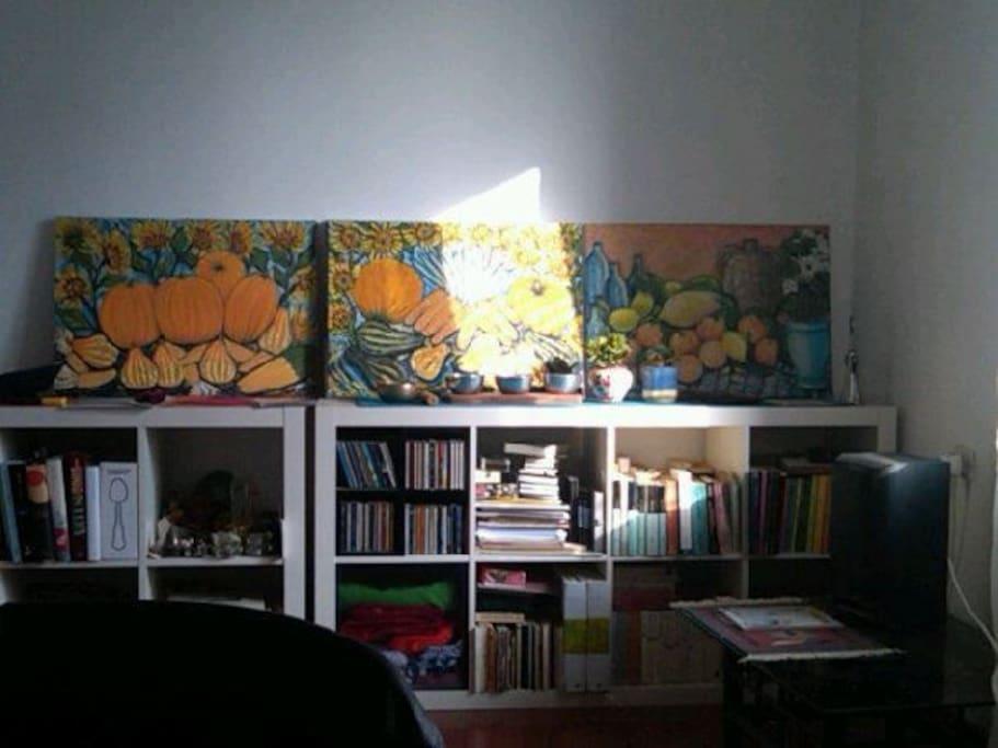 Il soggiorno con un sacco di libri e i quadri molto allegri di mio papà.