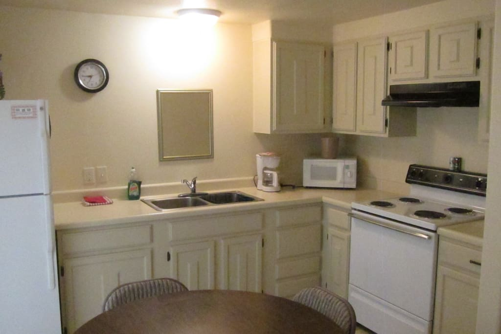 Spacious kitchen complete with dining and cooking sets.