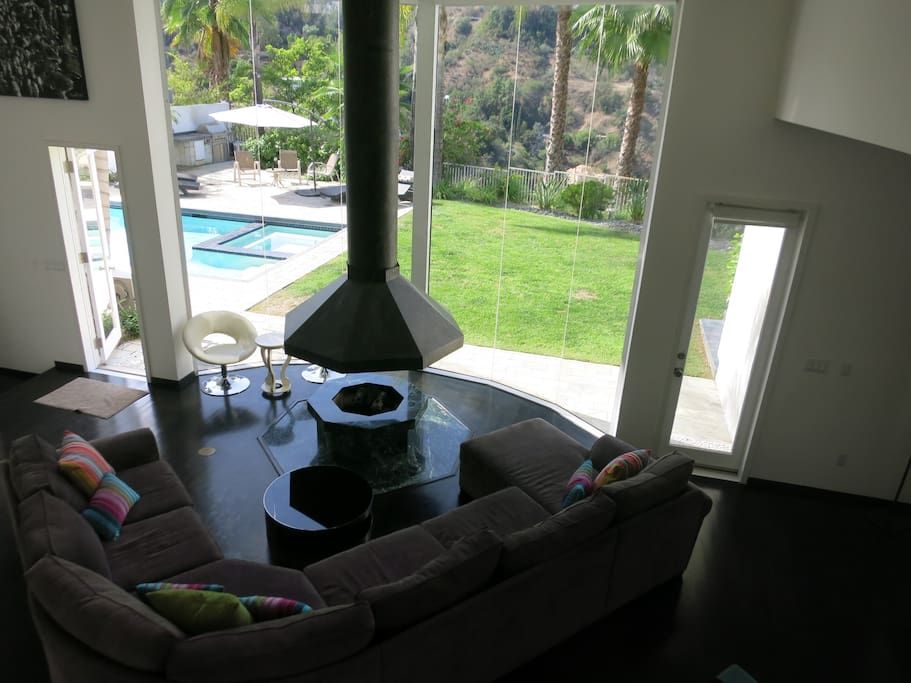 The living room with 25 ft ceilings looks out at the pool and the views beyond