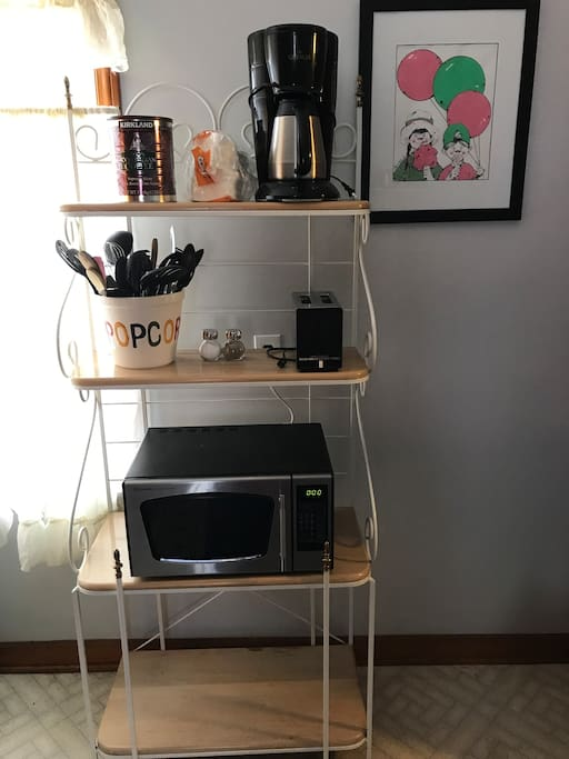 Kitchen - bakers rack with microwave, utensils, toaster, and coffee maker.