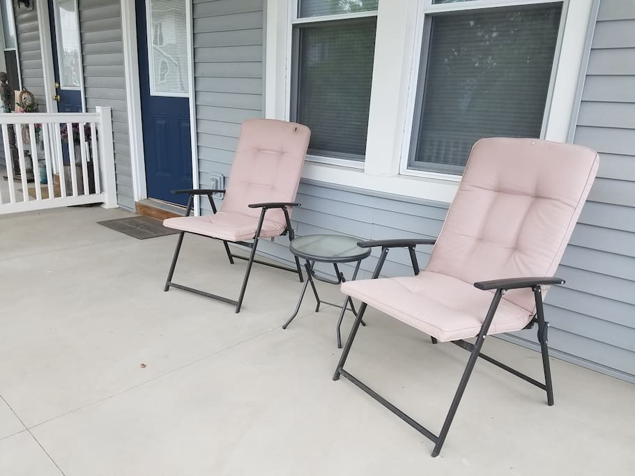 Two chairs on the front porch.