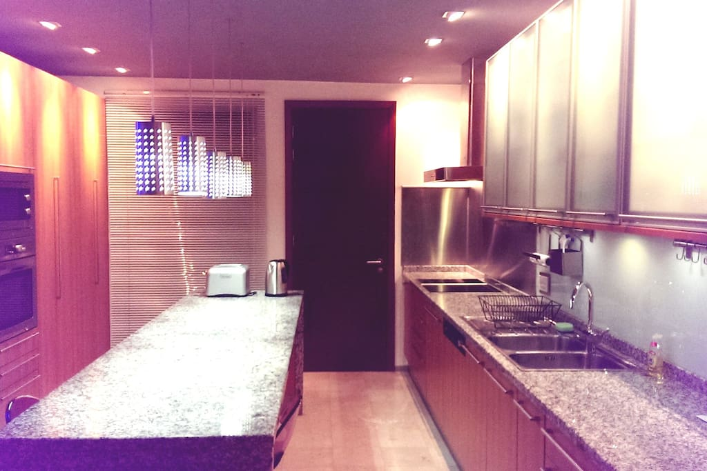 Open-plan kitchen with double fridge-freezer, dishwasher, induction hob, double sink with waste disposal unit.