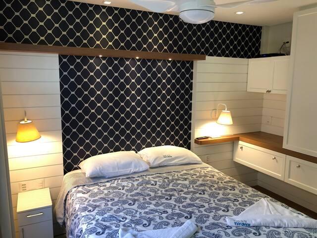 Suíte 01 com cama casal queen, móveis planejados, smart TV 32 pol, acesso internet banda larga, ar-condicionado split, ventilador no teto, cortinas black out, porta de acesso à varanda.