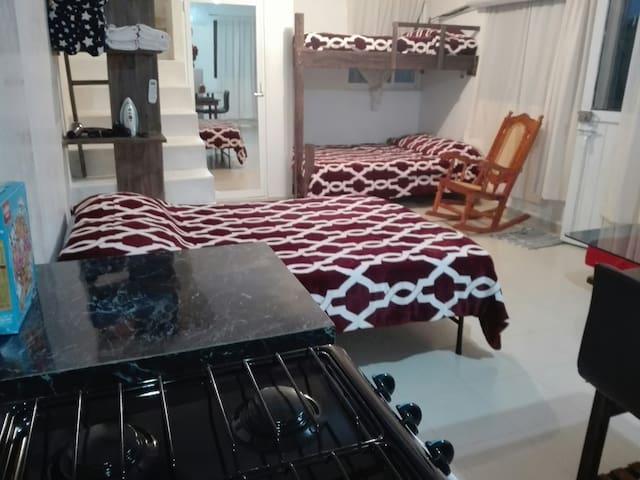 Vista desde la cocina, de derecha a izquierda: silla mecedora, litera, entrada al baño ( puerta con espejo), repisas con cobijas extras, cama matrimonial.