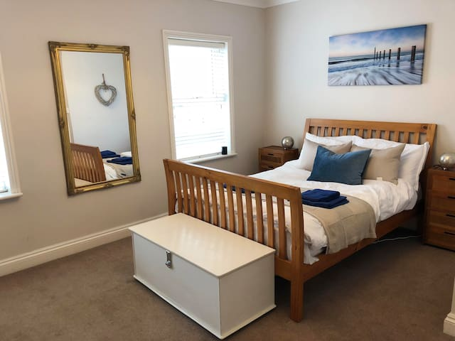 A comfortable bed in  a quiet and airy  bedroom