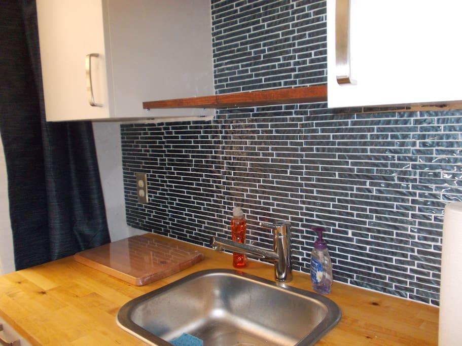 Close-up Kitchenette glass backsplash and butcher block countertop