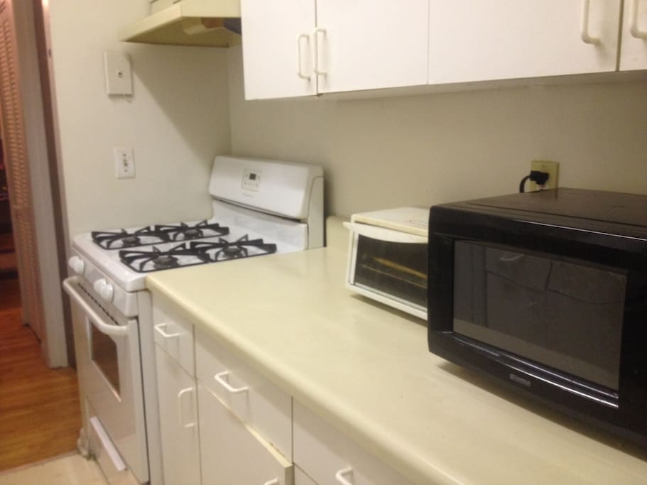 Kitchen with microwave, toaster oven, and gas stove.