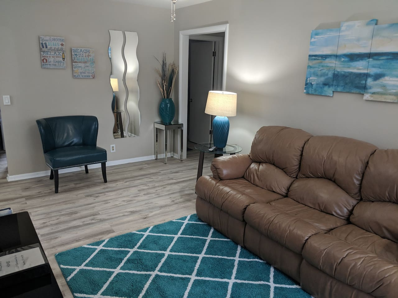 An leather couch and dark teal chair help make the living room inviting.