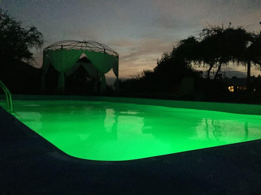 Es una fotografía nocturna con o iluminación de la piscina y las estrellas