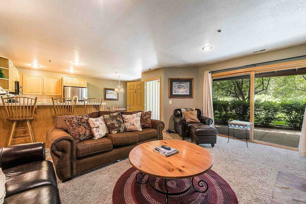"""The open concept living area features comfortable leather furnishings, 40"""" HDTV with Comcast TV and floor to ceiling stone fireplace."""