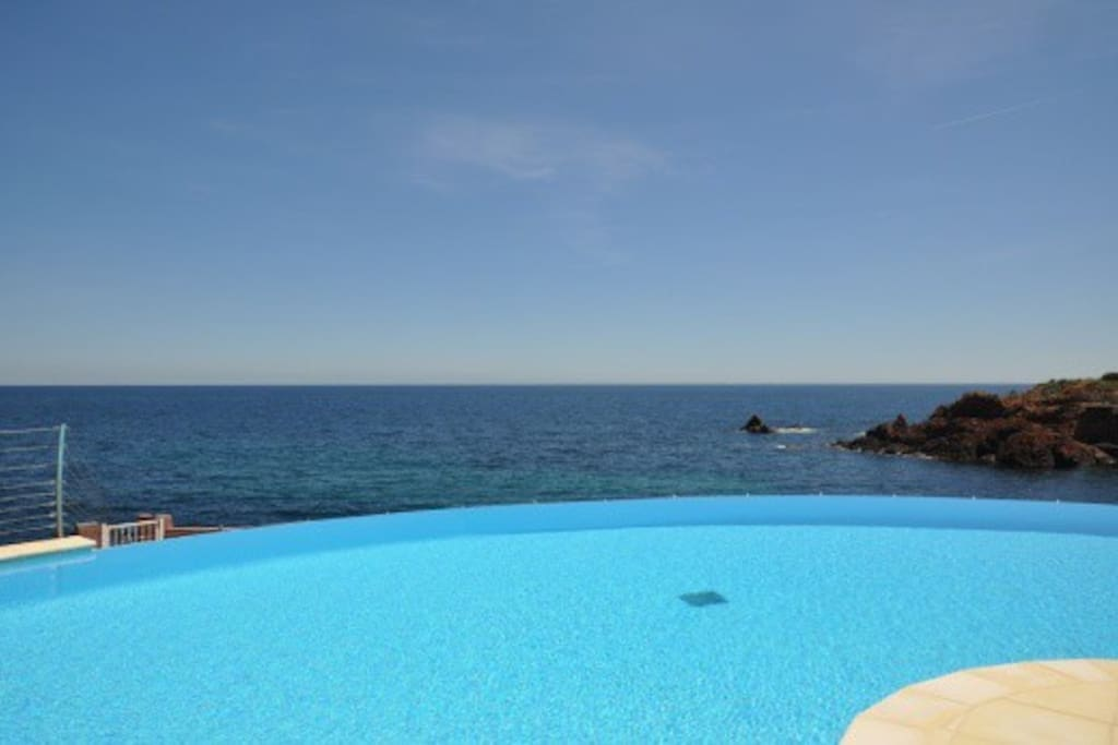 La magnifique piscine chauffée, à débordement, surplombant la mer.