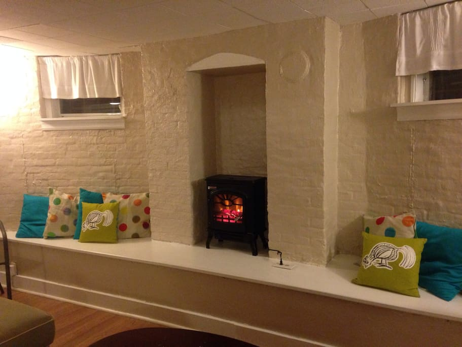 Electric fireplace in the living room. Bench seating along entire wall.