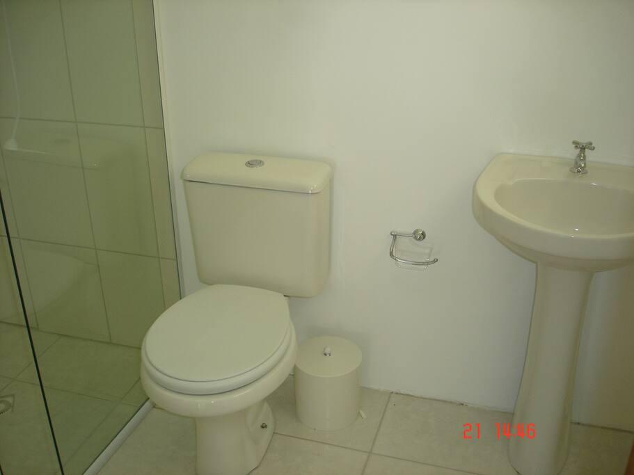 Banheiro com chuveiro elétrico e box de vidro
