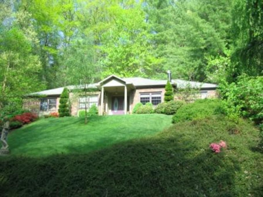 Wooded and landscaped front garden and home.