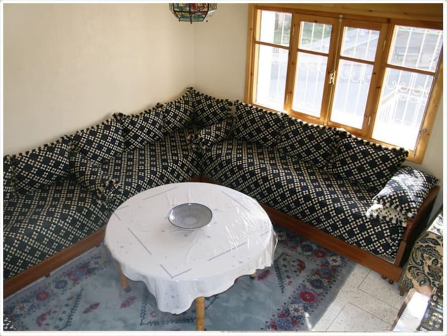 Salon marocain typique avec TV et climatisation