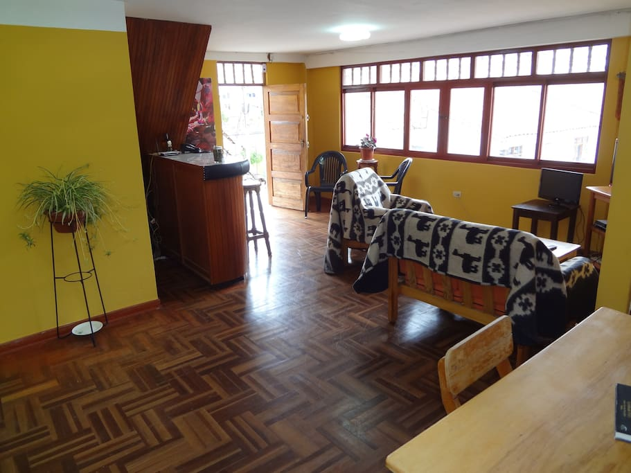 The living room is spacious and has a view of hills with Inca Ruins.