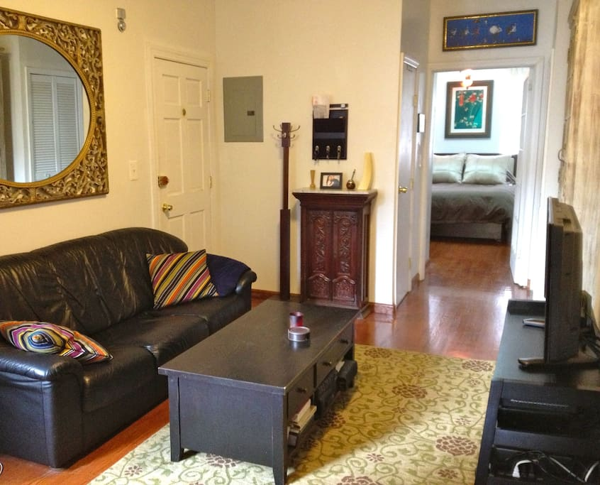 Living room with upscale, modern leather couch and antique furnishings, window a/c.
