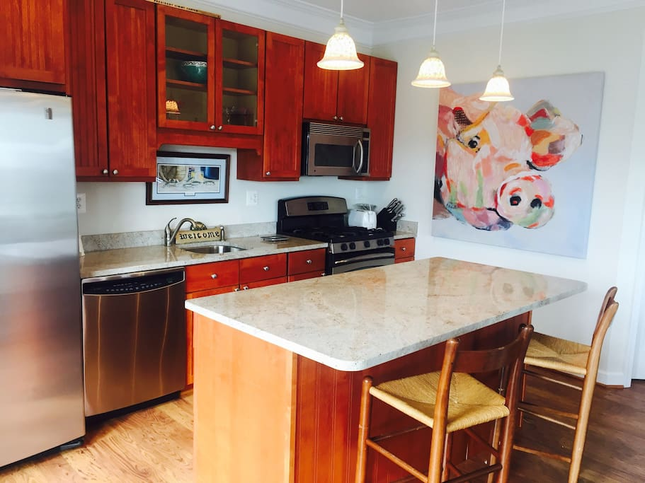 Bright and open kitchen with granite counters, island, stainless steel appliances, microwave and furnished with full set of dishes and cookware.